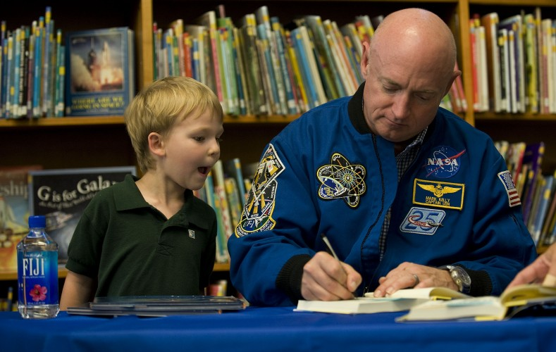 Wyatt Campbell, 5, of Winchester, looks over the shoulder of astronaut Mark Kelly as he autographs one of several children's books he purchased during Kelly's appearance on Tuesday at Powhatan School in Boyce.  Rich Cooley/Daily